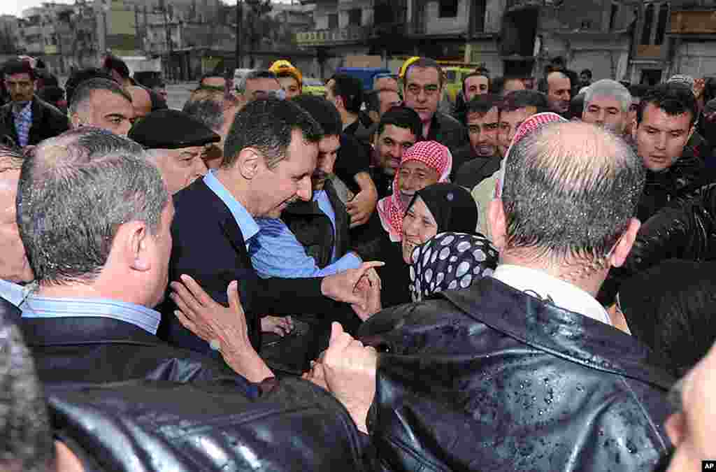 Syria's President Bashar al-Assad (C) smiles as he speaks to local supporters in Baba Amr. (Reuters/SANA)