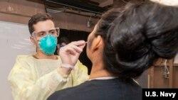 軍醫對羅斯福號航母上的水兵進行新冠病毒檢查(美國海軍2020年3月31日照片)
