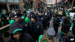 """FILE - Cleveland police walk with pedestrians as they patrol downtown, March 17, 2016. City officials say they are prepared for """"challenges"""" during the Republican Convention."""