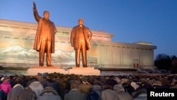 North Koreans bow to bronze statues of North Korea's late founder, Kim Il Sung, left, and late leader, Kim Jong Il, at Mansudae in Pyongyang in this picture provided by Kyodo, Dec. 16, 2014.