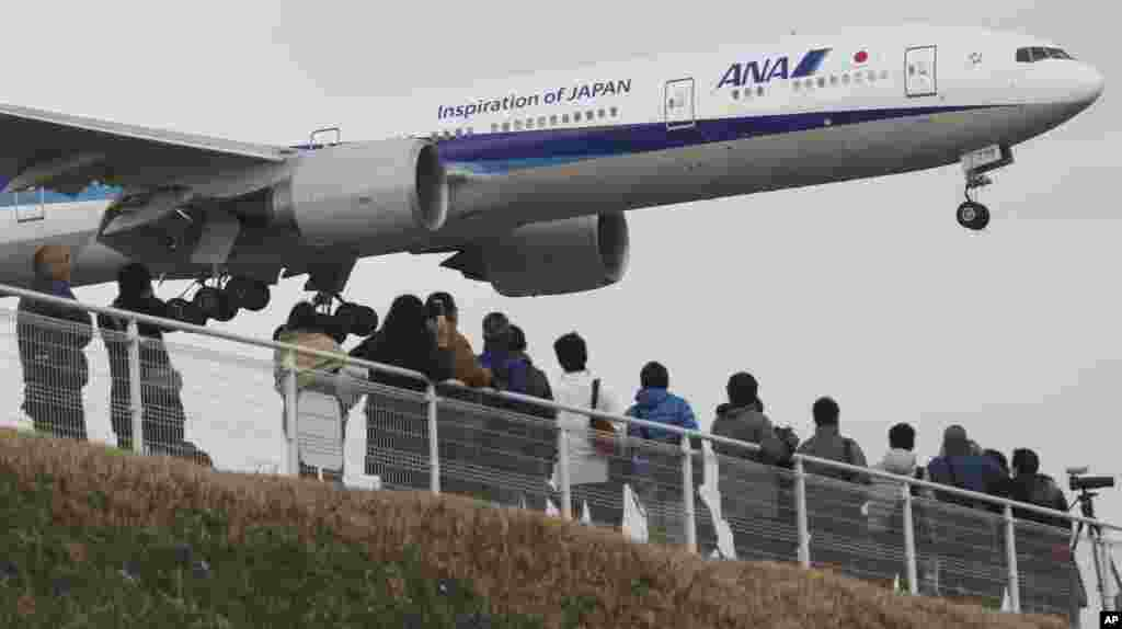 People enjoy watching a Japanese carrier All Nippon Airways' plane landing at the Narita International Airport from a popular viewing spot at Sakuranoyama Park in Narita, east of Tokyo, March 14, 2015.