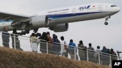 Quelques spectateurs en train de contempler un avion japonais atterrir à l'aéroport international de Narita, à partir du parc de Sakuranoyama, à l'est de Tokyo, 14 mars 2015.