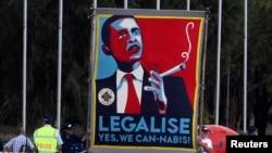 FILE - Marijuana activists use a sign to call on President Barack Obama to make the drug legal, Nov. 16, 2011.