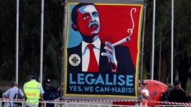 FILE - Marijuana activists use a sign to call on President Barack Obama to make the drug legal.