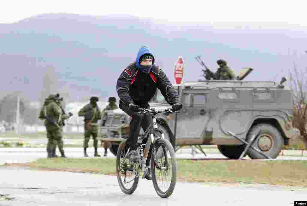 A man rides a bicycle as armed men, believed to be Russian serviceman, stand guard outside a Ukrainian military unit in the village of Perevalnoye, near Simferopol, Crimea, Ukraine, March 11, 2014.