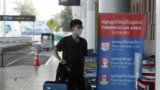 FILE - A tourist wearing a face mask enters an area of the scan at the quiet Phnom Penh International Airport in Phnom Penh, Cambodia, Friday, April 3, 2020. (AP Photo/Heng Sinith)