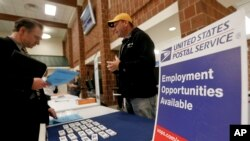 FILE - A recruiter from the postal service, right, speaks with a job fair attendee in Cheswick, Pa.