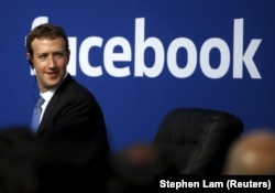 FILE - Facebook CEO Mark Zuckerberg is seen on stage during a town hall at Facebook's headquarters in Menlo Park, California, Sept. 27, 2015.