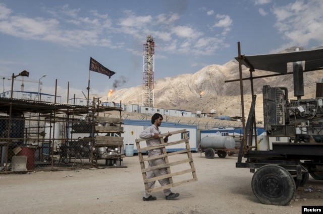 FILE - An Iranian laborer works at a unit of South Pars Gas field in Asalouyeh Seaport, north of Persian Gulf, Iran, Nov. 19, 2015. Due to sanctions relief, Iranian industries like oil and air travel have resumed international business.