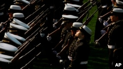 A midshipman lifts her face to the sun at the end of a formal dress parade by the Brigade of Midshipmen at the U.S. Naval Academy in Annapolis, Md. on Wednesday, April 7, 2010. (AP Photo/Jacquelyn Martin)