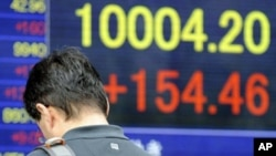 A man checks his mobile phone in front of an electric quotation board flashing the closing rate of the Tokyo Stock Exchange market in Tokyo on May 2, 2011