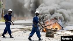 13일 아프리카 부룬디에서 경찰이 피에르 은쿠룬지자 대통령의 3선 출마를 반대하는 시위대가 설치한 바리케이트 앞을 지나고 있다.