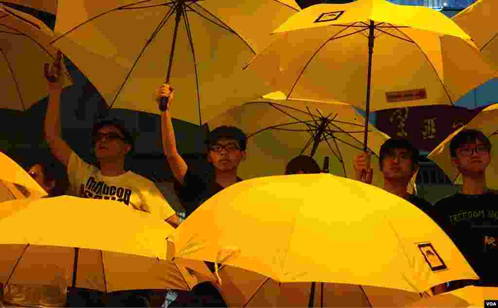 Joshua Wong (center left) and Alex Chow as they join other Umbrella Movement leaders unfurling umbrellas at the rally marking the one-month point since the beginning of the protests in Hong Kong (Ivan Broadhead/VOA).