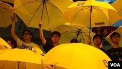 """资料照:黄之锋和周永康与其他""""雨伞运动""""领袖一起在集会上撑开黄色雨伞。一个月前,警方向争取民主的抗议人群发射催泪弹。(2014年10月28日)"""