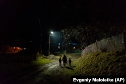 After a long working day Dr. Viktoria Mahnych and her two daughters walk to her parents to celebrate an eve of the Orthodox Christmas in Iltsi village, Ivano-Frankivsk region of Western Ukraine, Wednesday, Jan. 6, 2021. (AP Evgeniy Maloletka)