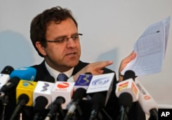 Afghan Finance Minister Hazrat Omar Zakhilwal shows documents during a news conference in Kabul, Aug. 7, 2012.