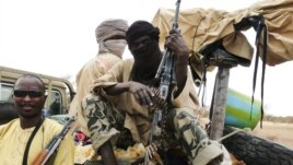 Militiamen from the Ansar Dine Islamic group sit on a vehicle in Gao in northeastern Mali, June 18, 2012.