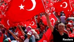 A man waves Turkey's national flag during the Democracy and Martyrs Rally, organized by Turkish President Tayyip Erdogan and supported by ruling AK Party (AKP), opposition Republican People's Party (CHP) and Nationalist Movement Party (MHP), to protest against last month's failed military coup attempt, in Istanbul, Turkey, August 7, 2016.