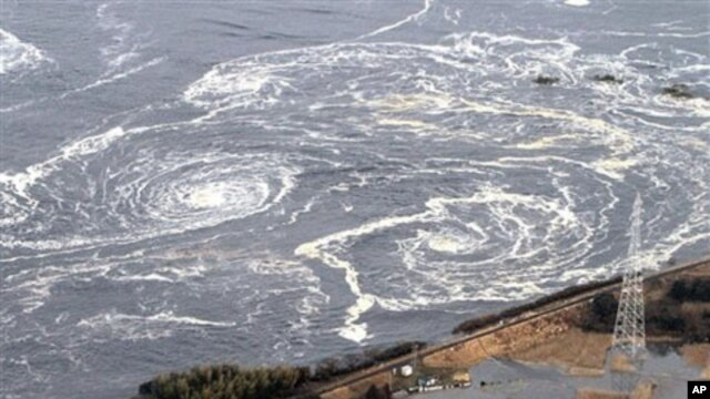 Swirls of waves approach to a coast in Iwaki, Fukushima Prefecture, northern Japan, March 11, 2011 after a powerful tsunami spawned by the largest earthquake in country's recorded history slammed the eastern coast