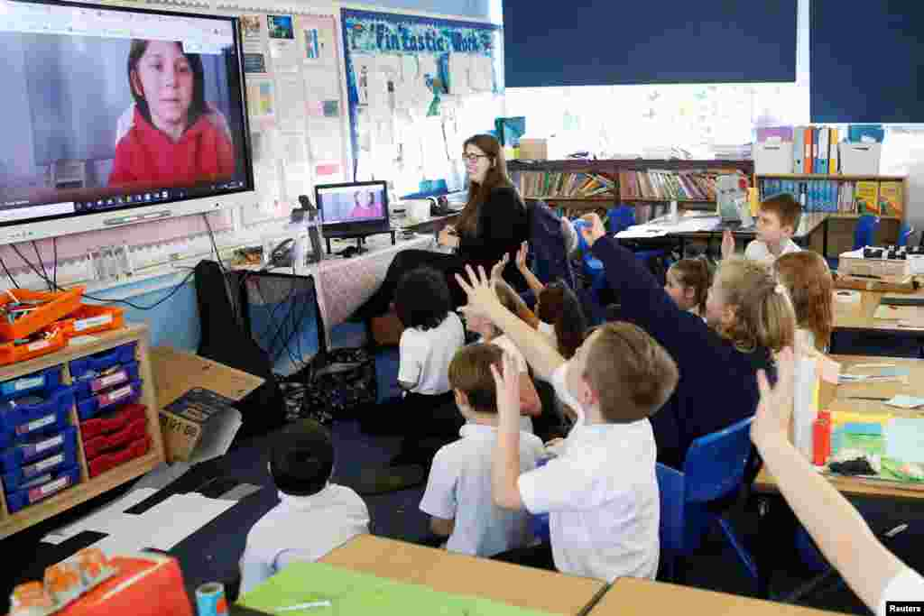 Students at Holne Chase School interact with a class member via the internet as his family is self-isolating amid the Covid-19 pandemic in Milton Keynes, Britain.