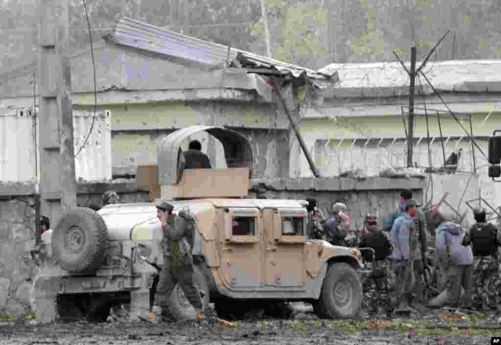 Afghan army and police surround the area after a multi-pronged attack on a police station in Jalalabad, Afghanistan, March 20, 2014.