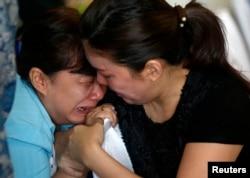 Family members of passengers onboard missing AirAsia flight QZ8501 cry at a waiting area in Juanda International Airport, Surabaya, December 29, 2014.