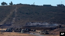 Turkey's forces' tanks and vehicles hold positions close to the border with Syria, near the town of Reyhanli, Oct. 9, 2017.