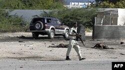 Binh sĩ Somalia bên cạnh thi thể của thường dân bị thiệt mạng trong vụ đánh bom nhắm vào sân bay Mogadishu, ngày 9/9/2010