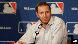 FILE - Two-time Cy Young Award winner Roy Halladay answers questions after announcing his retirement after 16 seasons in the major leagues with Toronto and Philadelphia at the MLB winter meetings in Lake Buena Vista, Fla., Dec. 9, 2013.