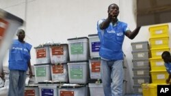 Staff organize ballot boxes and election materials as they are brought in from polling stations after counting at a National Election Commission warehouse in Monrovia, Liberia, October 12, 2011.
