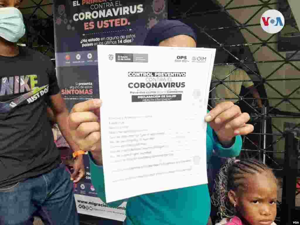"""Migrante muestra la ficha de """"Declaración de salud"""", un documento que incluye información de los desplazados con el objetivo de prevenir la propagación del coronavirus en Colombia."""