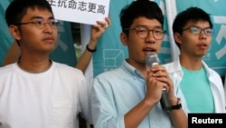 Newly elected lawmaker Nathan Law (C), student leaders Joshua Wong (R) and Alex Chow meet journalists outside a court before a hearing.