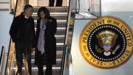 President Barack Obama and first lady Michelle Obama walk off Air Force One after arriving at O'Hare International Airport in Chicago, November 6, 2012.