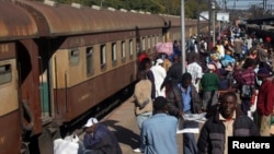 FILE: Commuters walk on a platform at a railway station in Harare, July 13, 2007. (Reuters)