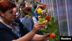 Porodica i prijatelji stavljaju cveće na kamion u kojem su preveženi posmrtni ostaci žrtava maskra u Srebrenici; 9. jul 2013.