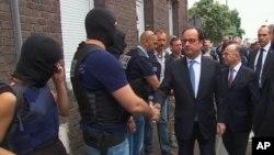 Presiden Perancis Francois Hollande bersalaman dengan anggota kepolisian di TKP serangan teroris di gereja di Normandy, Selasa (26/7).