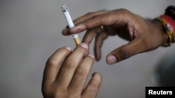 FILE - A man passes a cigarette to another as they sit on a pavement along a road in New Delhi, India, Aug. 18, 2015.