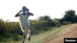 Mwanamke mmoja akikimbia kuokoa maisha yake baada ya shambulizi la anga huko Sudan Kusini. April 23, 2012. (Reuters).