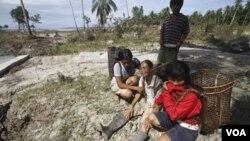 Seorang ibu menangisi suaminya yang meninggal akibat tsunami, didampingi dua anak perempuannya di Pulau Pagai, Mentawai.