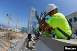 FILE - Telecommunications workers Chris Viens and Guy Glover install a new 5G antenna system made by Ericsson for AT&T's 5G wireless network in downtown San Diego, California, U.S., April 23, 2019.