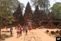 In this April 15, 2016, photo, tourists visit the Banteay Srey temple of the Angkor complex. The Angkor Wat temple is now off-limits to cars as authorities seek to ease traffic jams at the site that draws millions of tourists a year.