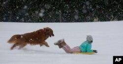 Una niña juega con su perro en la nieve en el estado de Carolina del Sur. Enero 3 de 2017.