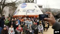 Группа школьников позироет на фоне модели Crew Exploration Vehicle