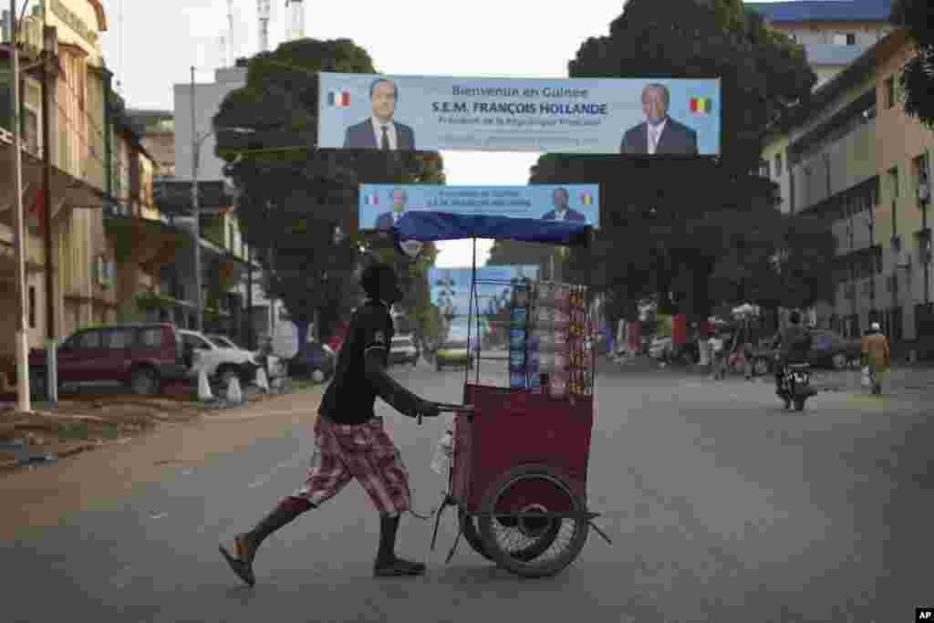 A Guinean street vendor pushes his cart under banners featuring French President Francois Hollande and his Guinean counterpart Alpha Conde in Conakry, Guinea, Wednesday, Nov. 26, 2014.