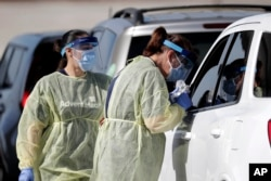 Healthcare workers conducts COVID-19 tests at a drive-thru coronavirus testing site, Tuesday, April 21, 2020, in Sanford, Fla. (AP Photo/John Raoux)