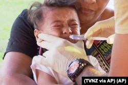 In this November 2019, image from video, a child gets vaccinated against measles at a health clinic in Apia, Samoa.