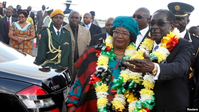 Zimbabwe's President Robert Mugabe, right, welcomes Malawian counterpart Joyce Banda upon her arrival at Harare International Airport, April 23, 2013.