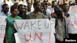 Sudanese protesters hold signs during a demonstration in Tel Aviv against the deportation of migrants from South Sudan, June 10, 2012.