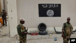 Chadian soldiers stand at a checkpoint in front of a Boko Haram flag in the Nigerian city of Damasak, March 18, 2015. (AP Photo/Jerome Delay)