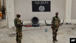 Chadian soldiers stand at a checkpoint in front of a Boko Haram flag in the Nigerian city of Damasak, March 18, 2015.